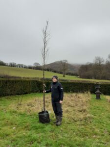 Warden Standing holding tree